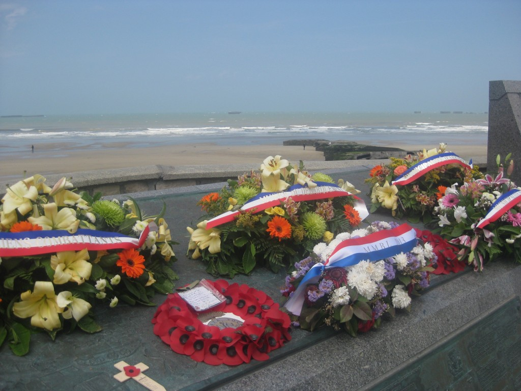 Fresh flowers commemorating D-Day at Arromanches. Beyond, you can see remains of the Mulberry artificial harbor, which was built by the Allies to supply the troops. I snapped this photo on the anniversary of D-Day, June, 2014. The French still honor that day.