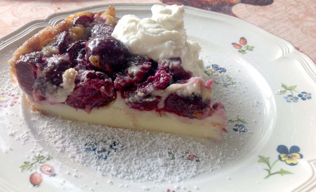 A slice of cherry clafouti. Spiked whipped cream is a must!